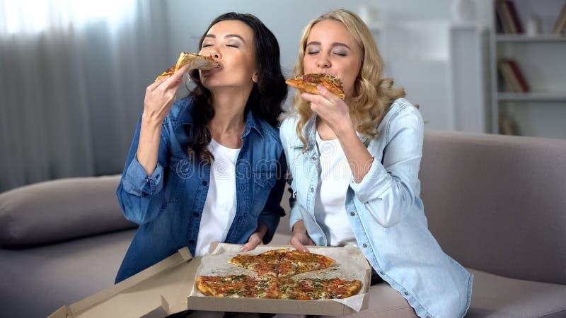 Tv? hungriga kvinnliga studenter som inomhus tycker om enorm l?cker pizza, matleverans royaltyfri bild