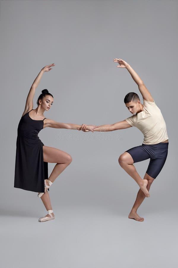 Tv? idrotts- moderna balettdans?rer poserar mot en gr? studiobakgrund arkivbild