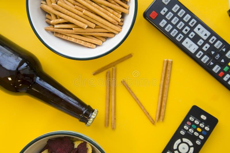 TV inscription, beer and remote controls royalty free stock photography