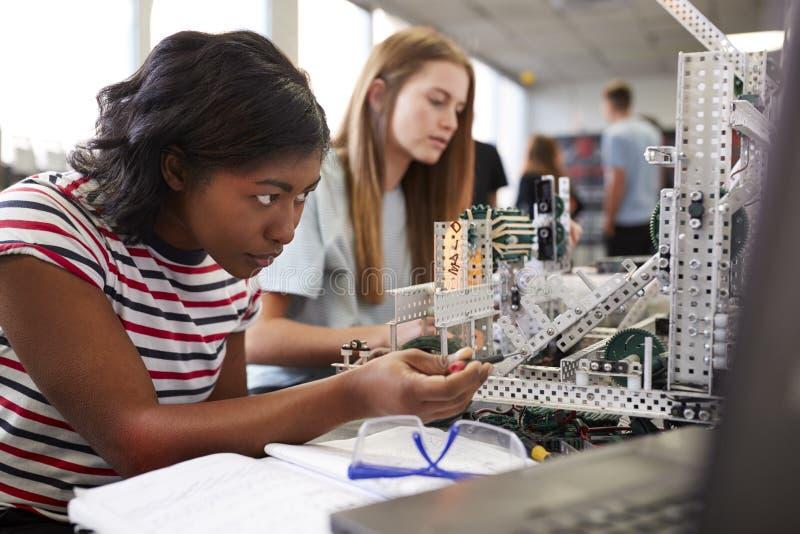 Tv? kvinnliga h?gskolestudenter som bygger maskinen i vetenskapsrobotteknik eller iscens?tter grupp arkivbild