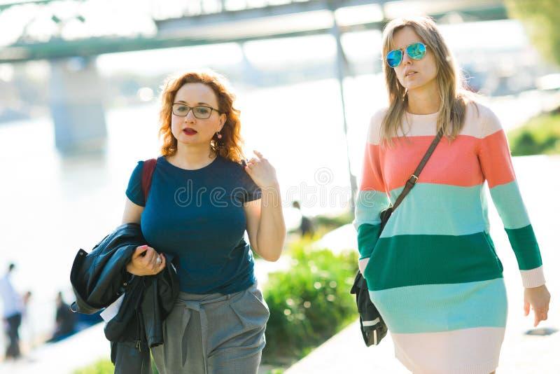 Tv? kvinnor som promenerar stranden arkivfoto
