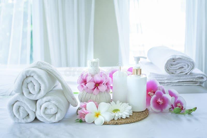 Tv?l-, handduk- och blommasnowdrops Spa behandlinguppsättning och aromatisk massageolja på sängmassage Thailändsk inställning för arkivfoton