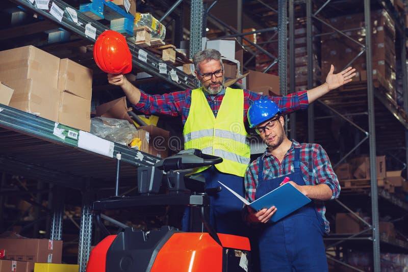 Tv? lagerarbetare som fyller i dokument arkivfoton
