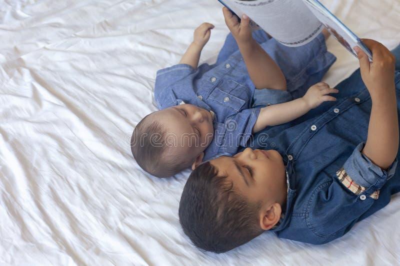 Tv? lilla br?der som l?ser en bok Begynnande ungar som ligger p? s?ngen och att l?sa sagan, innan att sova L?sa en kort ber?ttels royaltyfri foto