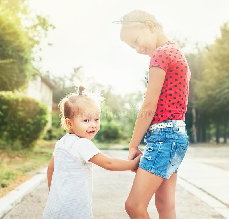 Tv? lilla systrar som tillsammans g?r i sommarstad, parkerar Familjev?rderingbegreppsfoto arkivfoto