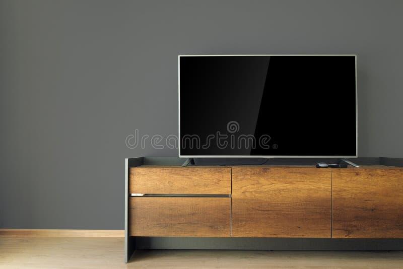 TV llevada en soporte de la TV con la pared negra foto de archivo