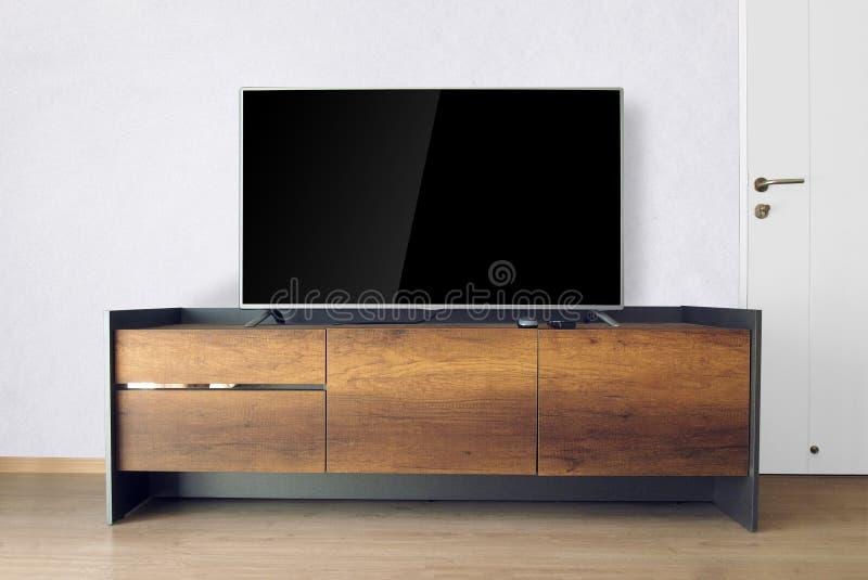 TV llevada en soporte de la TV en sitio vacío con el muro de cemento blanco decoración fotos de archivo