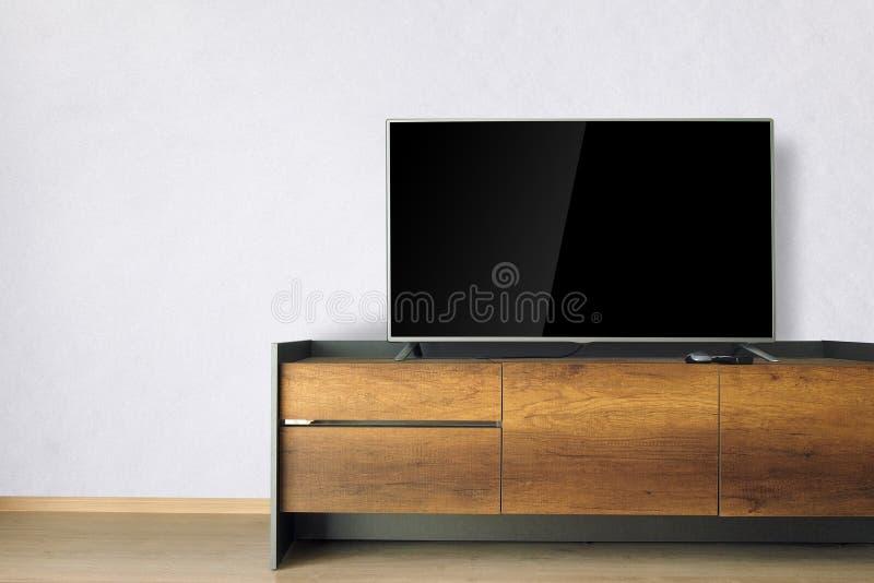TV llevada en soporte de la TV en sitio vacío con el muro de cemento blanco decoración fotografía de archivo libre de regalías