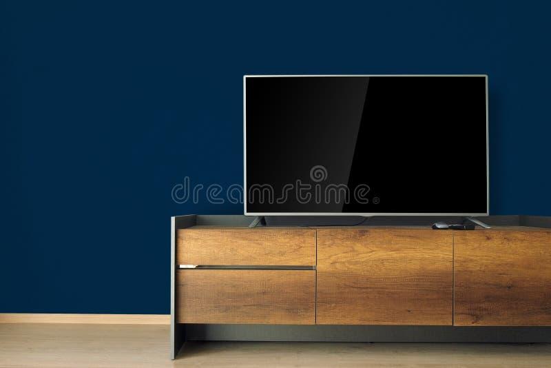 TV llevada en soporte de la TV en sitio vacío con la pared azul adorne en lof fotos de archivo