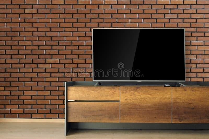 TV llevada en soporte de la TV en sitio vacío con la pared de ladrillo roja adorne i fotografía de archivo