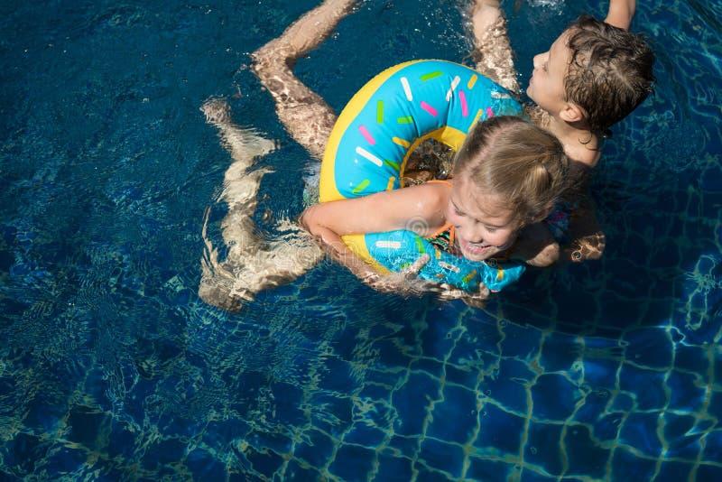 Tv? lyckliga barn som spelar p? simbass?ngen p? dagtiden royaltyfria foton