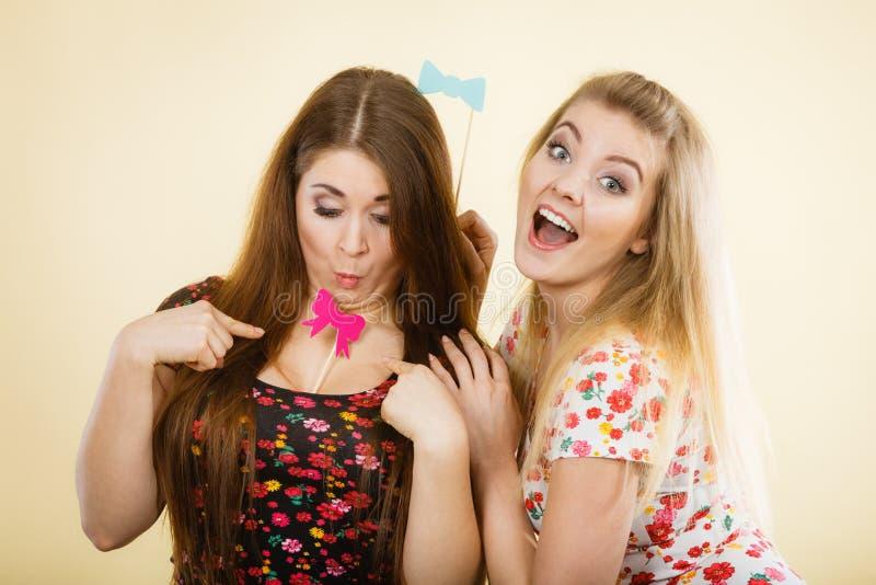 Tv? lyckliga kvinnor som rymmer karnevalaccessoies p? pinnen arkivfoto