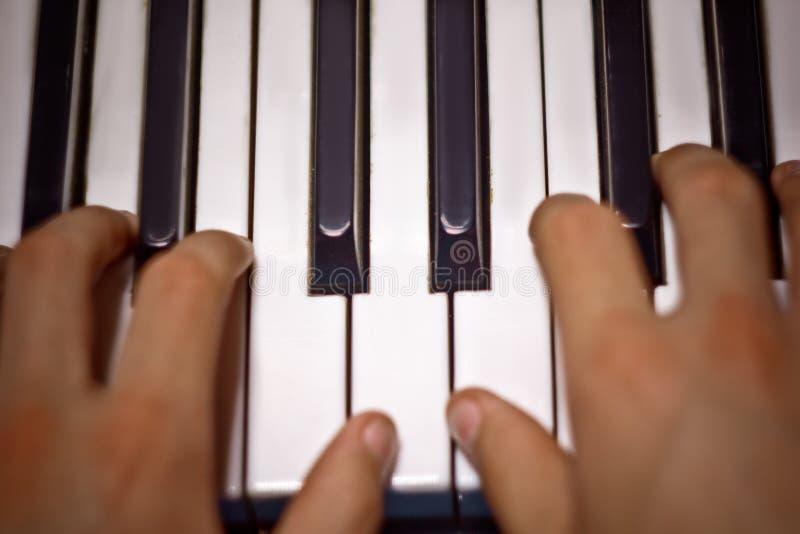 Tv? manliga h?nder p? pianot g?mma i handflatan l?gn p? tangenterna och spelar tangentbordinstrumentet i musikskolan studenten l? arkivbild