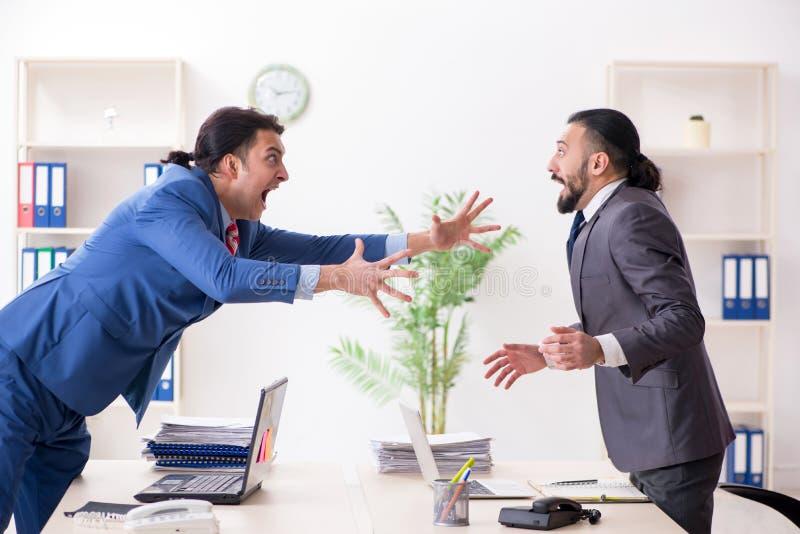Tv? manliga kollegor i kontoret royaltyfri fotografi