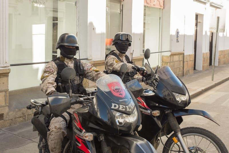 Tv? medlemmar av den speciala deltapolisstyrkan som sitter p? deras h?ga drev mopeder i en sidogata i Sucre Bolivia arkivfoto