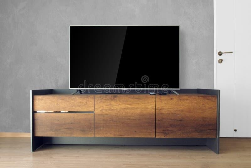 TV menée sur le support de TV dans la chambre vide avec le mur en béton décorez dedans images stock
