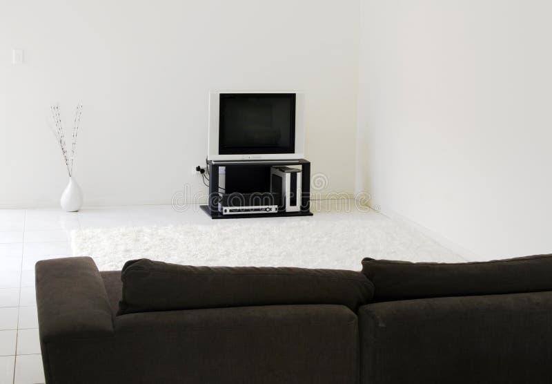 TV In Modern Living Room. White Tiles, Rug, Dark Sofa stock photography