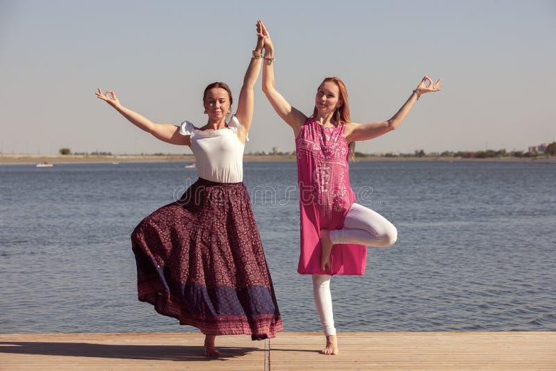 Tv? mogna kvinnor som h?ller passformen, genom att g?ra yoga i sommaren royaltyfri fotografi