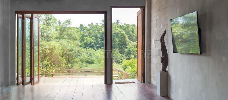 Tv na betonowej ścianie z wysokimi okno w pustym żywym izbowym wnętrzu obraz stock