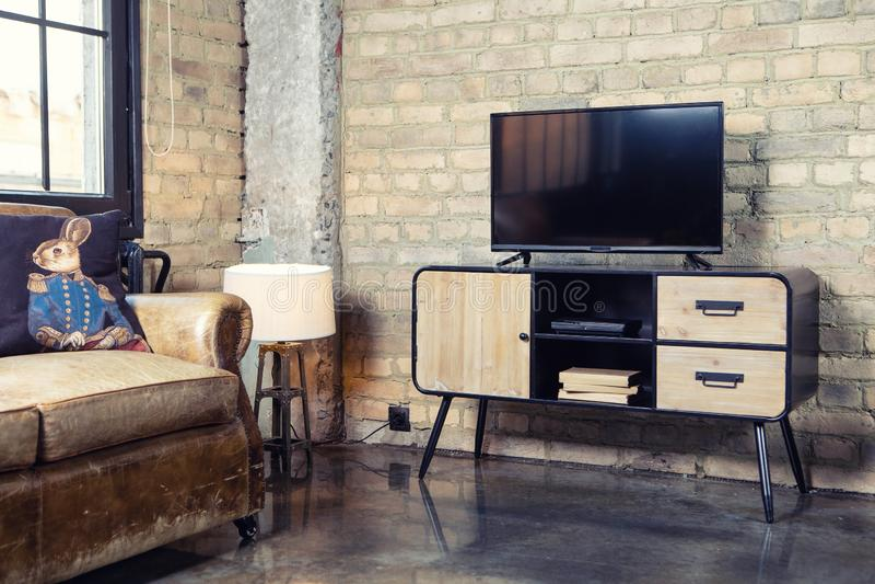 TV nell'interno nel retro stile del sottotetto sul comodino immagine stock