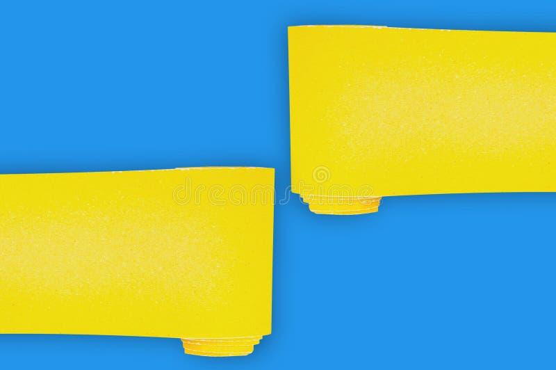 Tv? nya rullar av gul slipande sandpapper f?r rastertr?- eller metallobjekt p? den bl?a tabellen i seminarium kopiera avst?nd f?r arkivbild