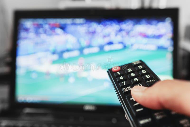 TV, partita di calcio, film ed ecc di sorveglianza Mano facendo uso di telecomando fotografia stock
