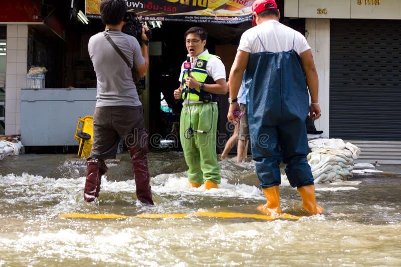 TV-personas que hacen un informe sobre la inundación imagen de archivo libre de regalías
