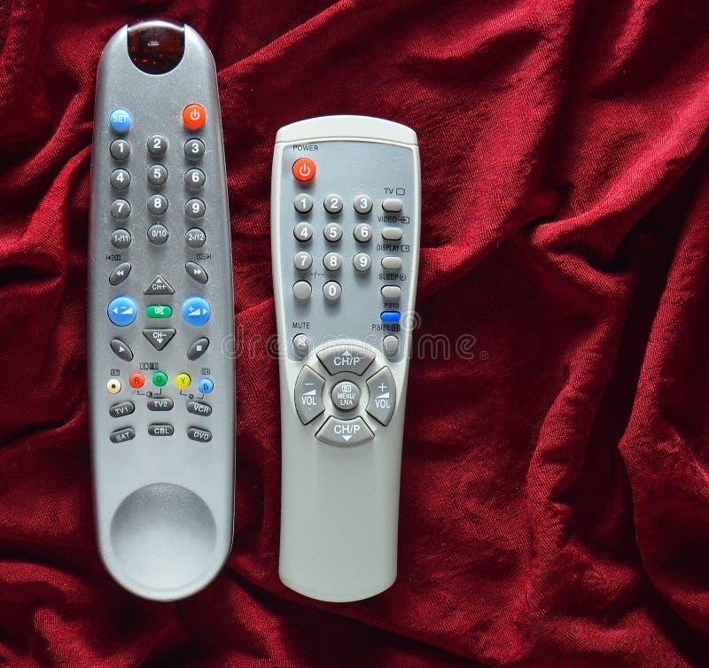 TV piloci do tv na czerwonym jedwabniczym tle fotografia royalty free