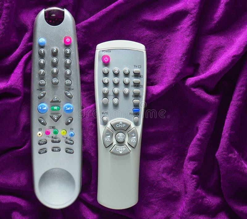 TV piloci do tv na fiołkowym jedwabniczym tle zdjęcia stock