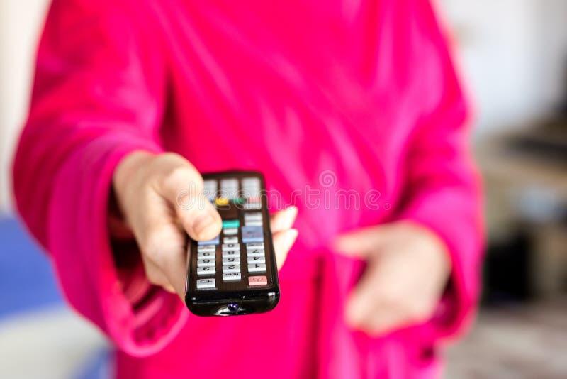 TV pilot do tv trzymający w women& x27; s ręki Wyłaczać kanały na t fotografia royalty free