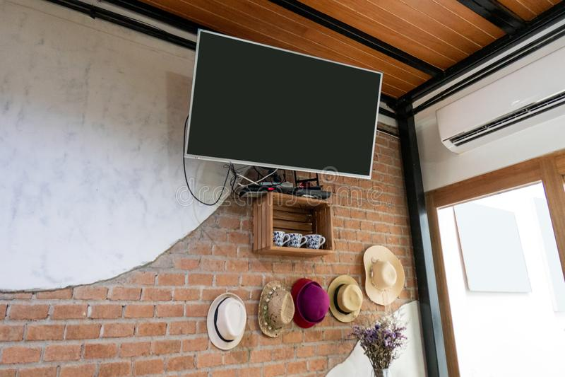 TV plate accrochant sur le mur de briques photographie stock libre de droits