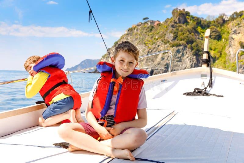 Tv? pojkar f?r liten unge, b?sta v?n som tycker om segelb?ten, snubblar Familjsemestrar p? havet eller havet p? solig dag Barn arkivbilder