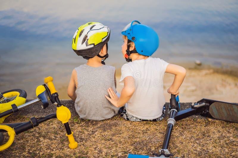 Tv? pojkar sitter p? kusten av sj?n, n?r de har ridit en cykel och en sparkcykel royaltyfria foton