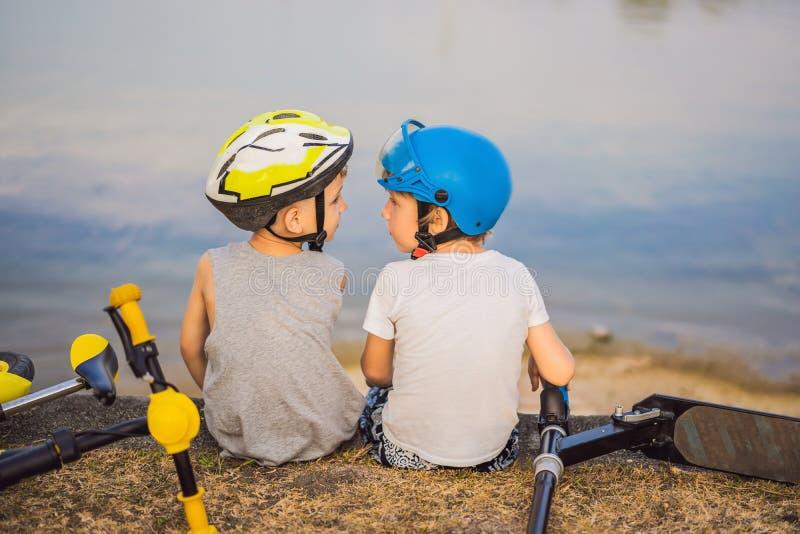Tv? pojkar sitter p? kusten av sj?n, n?r de har ridit en cykel och en sparkcykel royaltyfri foto