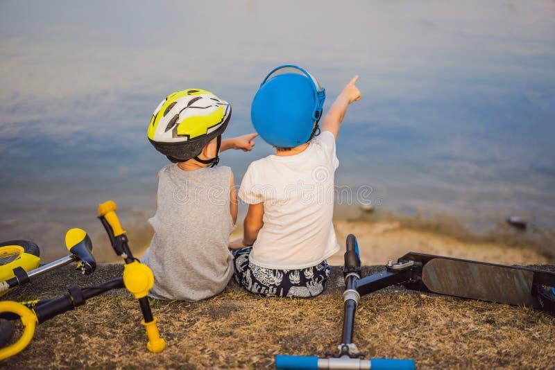 Tv? pojkar sitter p? kusten av sj?n, n?r de har ridit en cykel och en sparkcykel royaltyfri fotografi