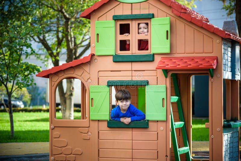 Tv? pyser som tillsammans spelar och har gyckel Livsstilfamilj?gonblick av syskon p? lekplats Ungev?nner spelar p? tr?d arkivbilder