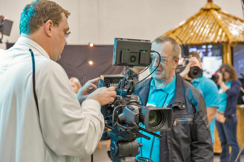 TV and Radio International Fair in Kiev, Ukraine. People visit booth with professional camers on TV and Radio International Fair in ACCO International EC. It is royalty free stock photo