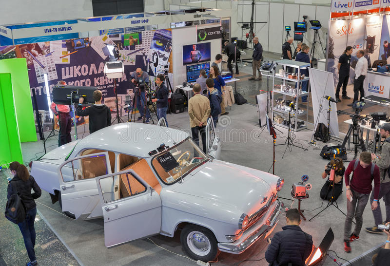 TV and Radio International Fair in Kiev, Ukraine. People visit School of Authors Cinema and TV booth with highlighted in multicolored lights GAZ-21 Volga royalty free stock image