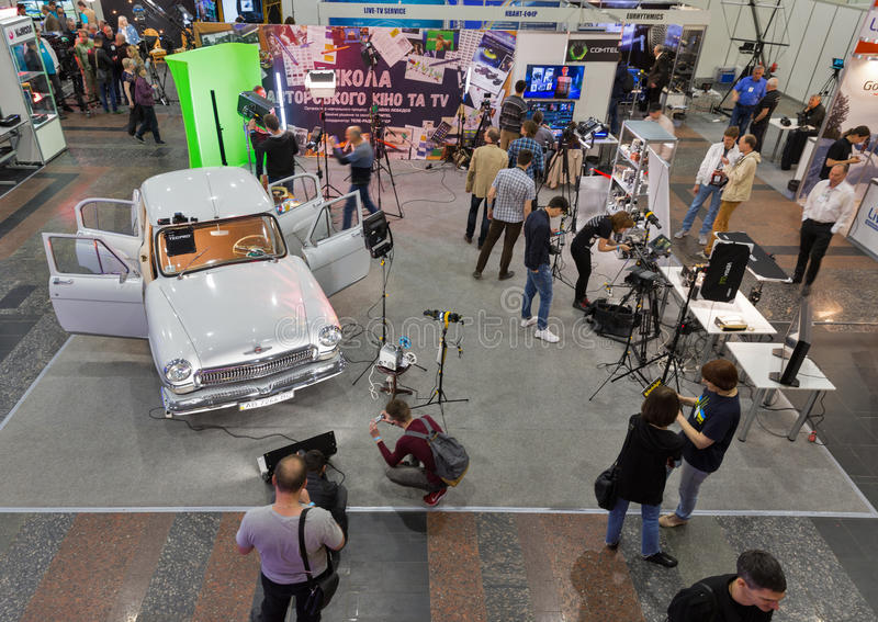 TV and Radio International Fair in Kiev, Ukraine. People visit School of Authors Cinema and TV booth with highlighted in multicolored lights GAZ-21 Volga royalty free stock photos