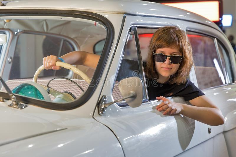 TV and Radio International Fair in Kiev, Ukraine. Young woman in GAZ-21 Volga vintage car on School of Authors Cinema and TV booth during TV and Radio stock photos