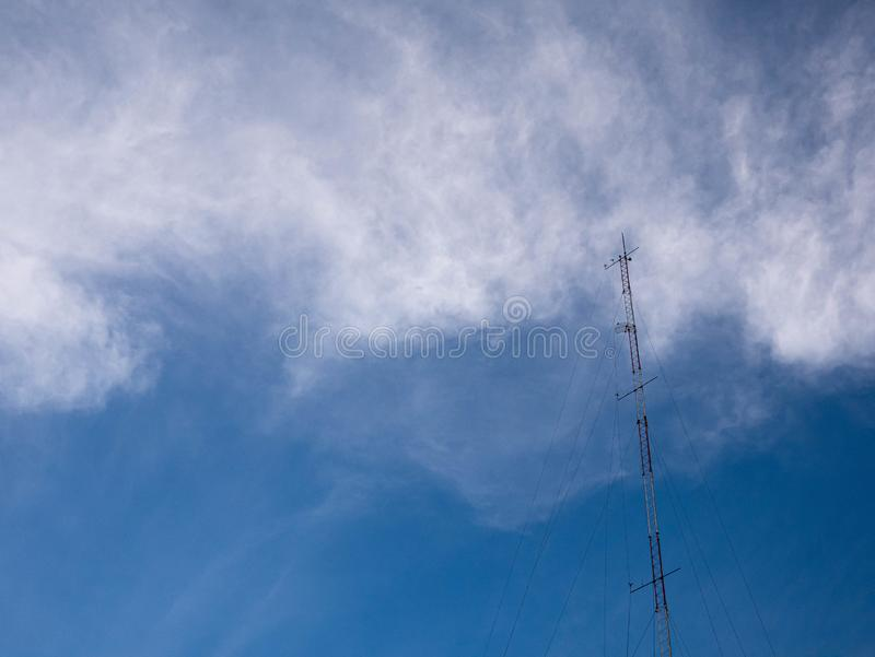TV and radio pole telecommunication antenna on clouds and blue sky background stock photo