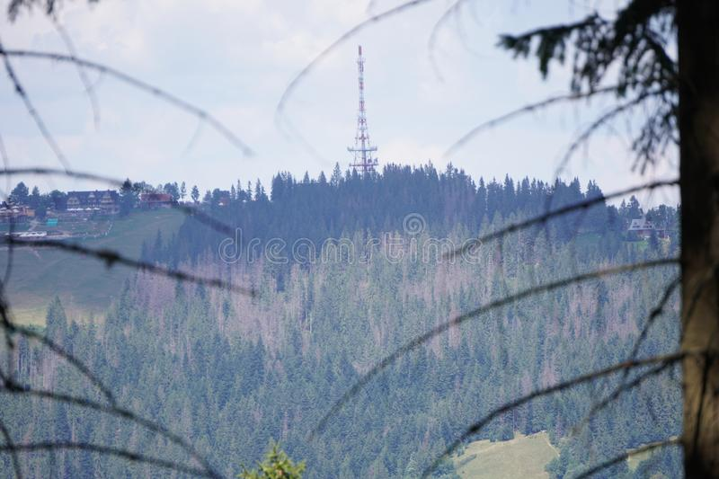 TV-radio tower on top of the mountain. Antenna behind the mountain panoramic view. Smog and fog in the forest. TV-radio tower on top of mountain. Antenna behind royalty free stock image