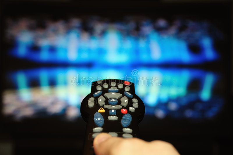 TV remote. Channel surfing in front of a blue screen royalty free stock photos