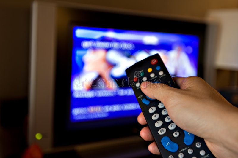 TV remote control. Hand pointing a tv remote control towards the television