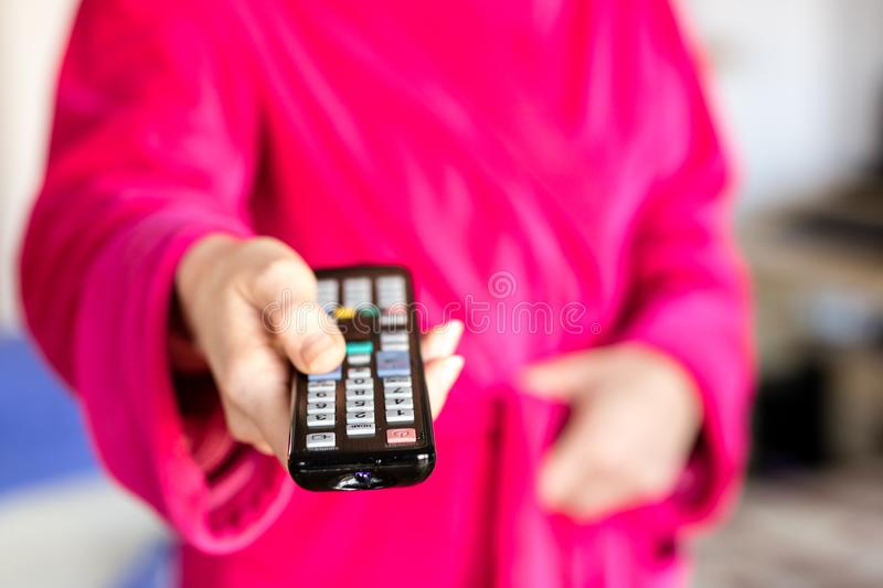TV remote control held in women& x27;s hands. Switching channels on t royalty free stock photography