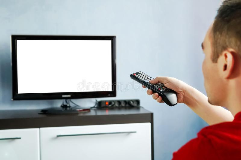 TV remote control in male hand in front of widescreen TV set with blank screen on blue wall background. Young guy switches channel stock photo