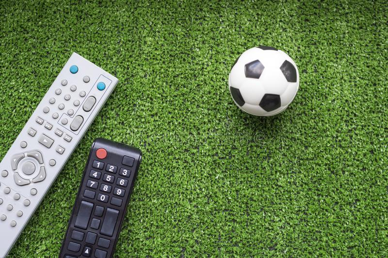 TV remote control and soccer ball on the green grass. Program football concept stock image