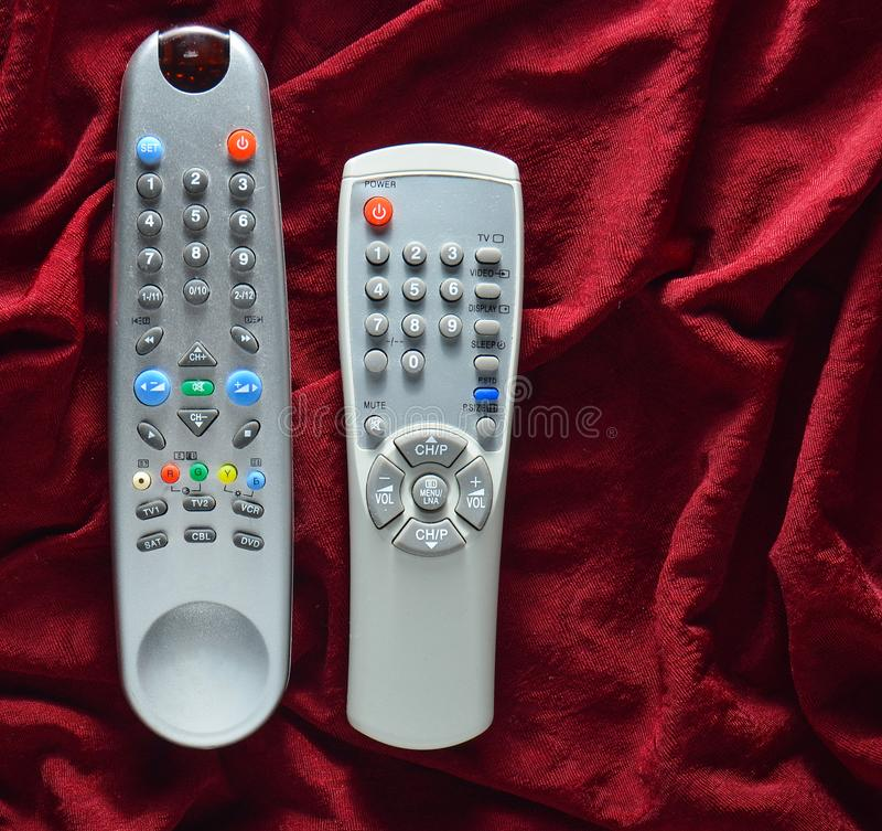 TV remote controls on a red silk background. royalty free stock photography