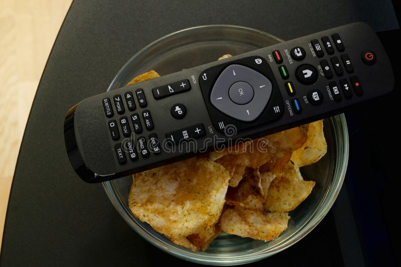Tv remote lies on top of a glass bowl filled with crunchy dill and chive potato chips stock images