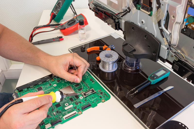 TV repair in the service center, engineer soldering electronic components. On board royalty free stock photos